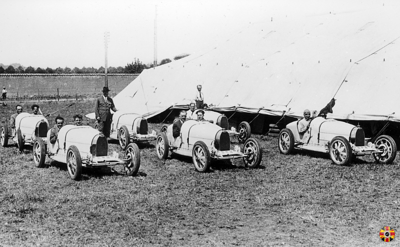 Ettore Bugatti proudly shows new car, Bugatti Type 35, at staging area of 1924 Lyon Grand Prix.